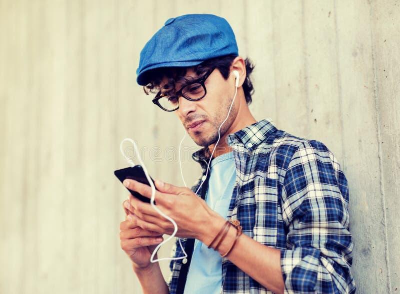Mann mit Kopfh?rern und h?render Musik des Smartphone stockfotos