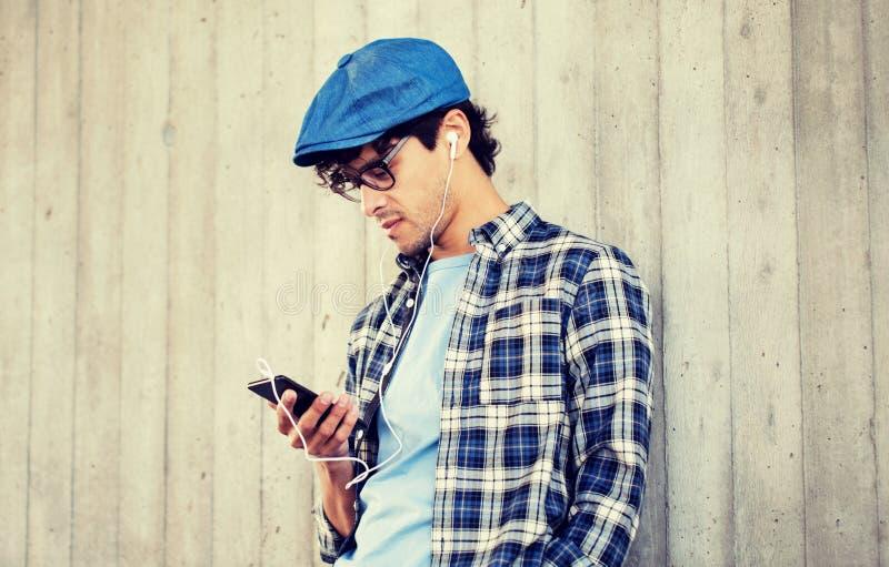 Mann mit Kopfh?rern und h?render Musik des Smartphone lizenzfreie stockfotografie