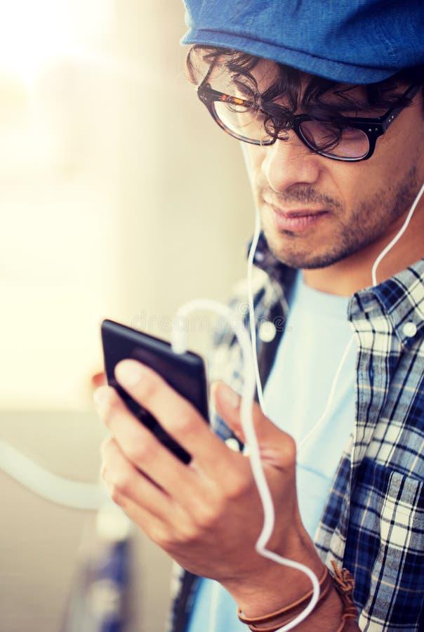 Mann mit Kopfh?rern und h?render Musik des Smartphone lizenzfreies stockbild