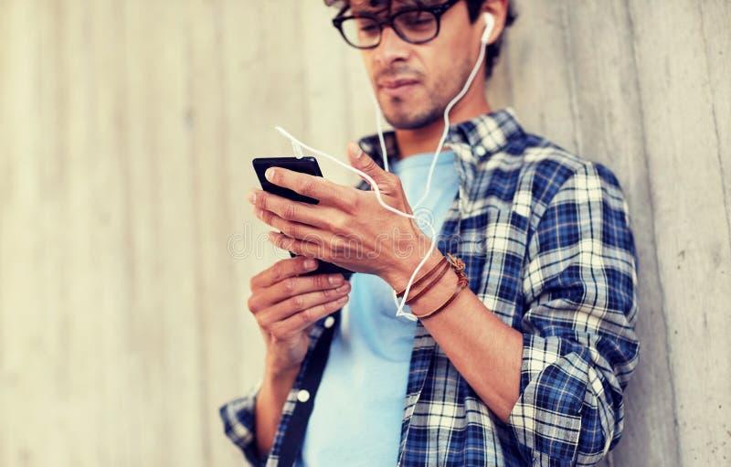 Mann mit Kopfh?rern und h?render Musik des Smartphone lizenzfreies stockfoto