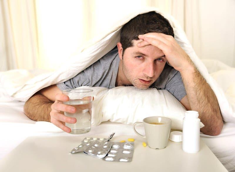 Mann mit Kopfschmerzen und Kater im Bett mit Tabletten stockfoto