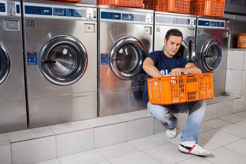 Mann mit Korb der Kleidung, die am Waschautomaten sitzt lizenzfreie stockbilder