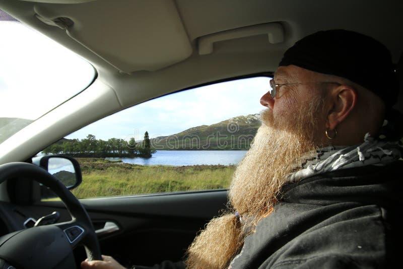 Mann mit langem Bart, Antriebe im Auto in den Hochländern, Hochland von Schottland, nahe Loch Ness lizenzfreie stockfotografie