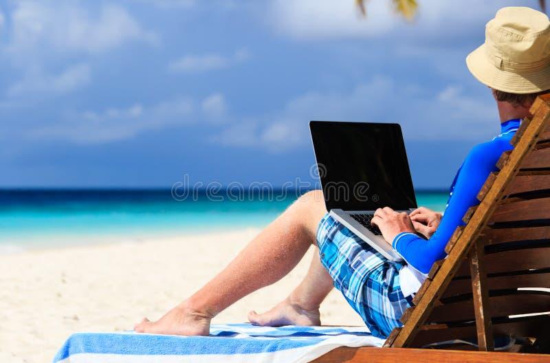 Mann mit Laptop auf tropischen Ferien stockbild