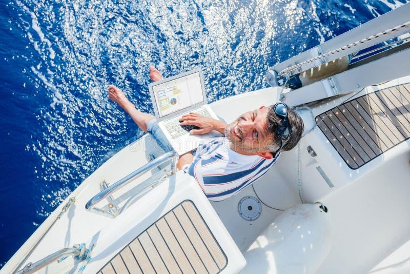 Mann mit Laptop-Computer auf Segelboot stockfoto