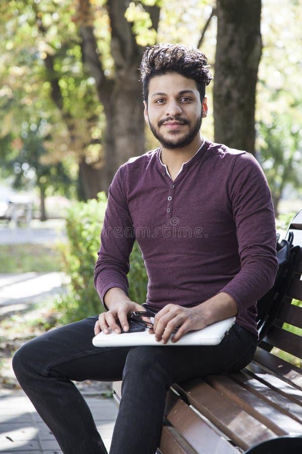 Mann mit Laptop am Sommerpark am hellen Tag lizenzfreie stockfotografie