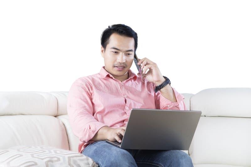 Mann mit Laptop sprechend auf Smartphone lizenzfreies stockfoto