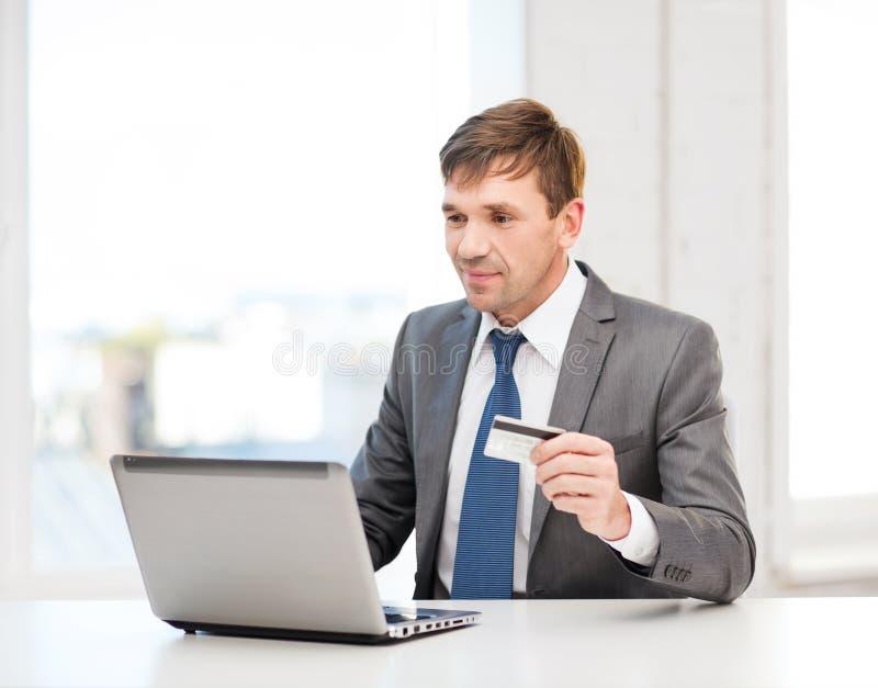 Mann mit Laptop und Kreditkarte im Büro lizenzfreies stockbild