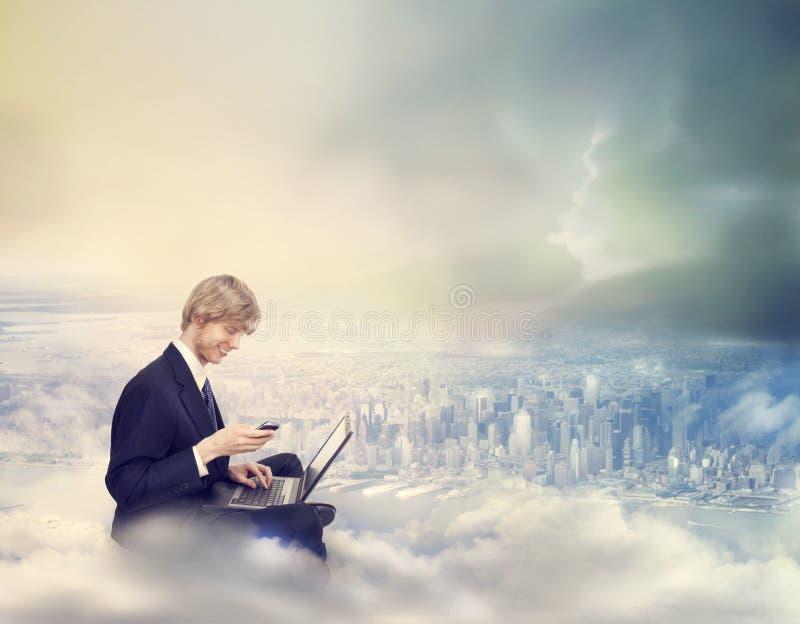 Mann mit Laptop und Telefon oben auf die Stadt lizenzfreie stockbilder