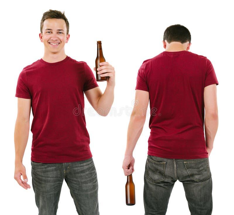 Mann mit leerem Burgunder-Hemd und trinkendem Bier lizenzfreie stockbilder