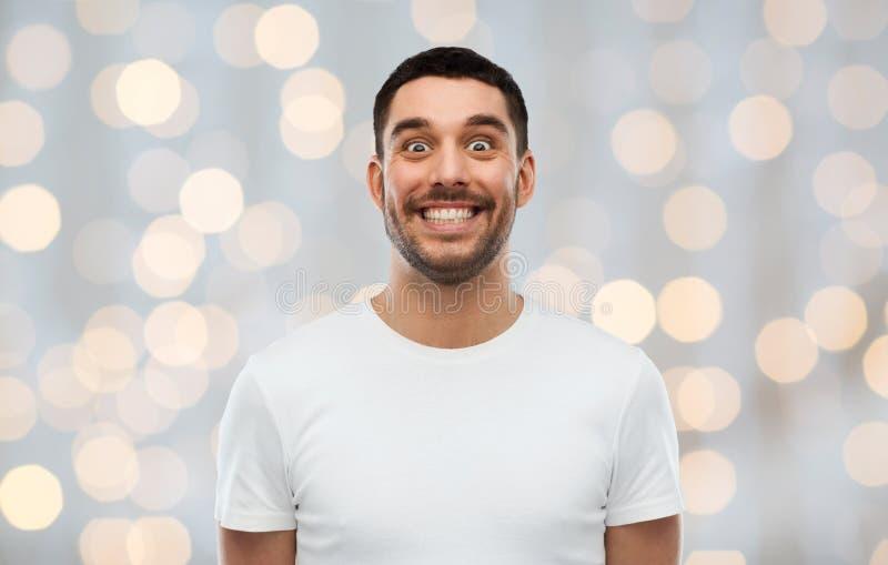 Mann mit lustigem Gesicht über Lichthintergrund lizenzfreie stockbilder
