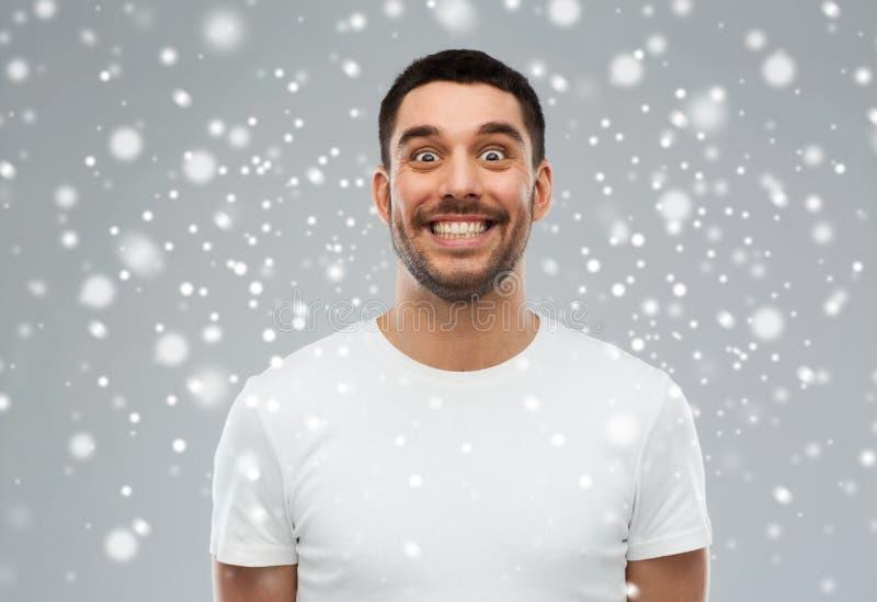 Mann mit lustigem Gesicht über Schnee stockfotografie