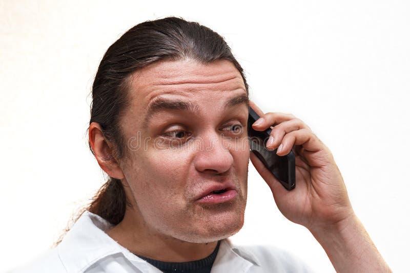 Mann mit lustigem Gesicht sprechend auf dem Smartphone lizenzfreie stockfotos