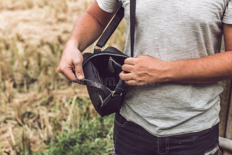 Mann mit Luxus-snakeskin Pythonlederhandtasche Bali-Inselhintergrund stockfotos