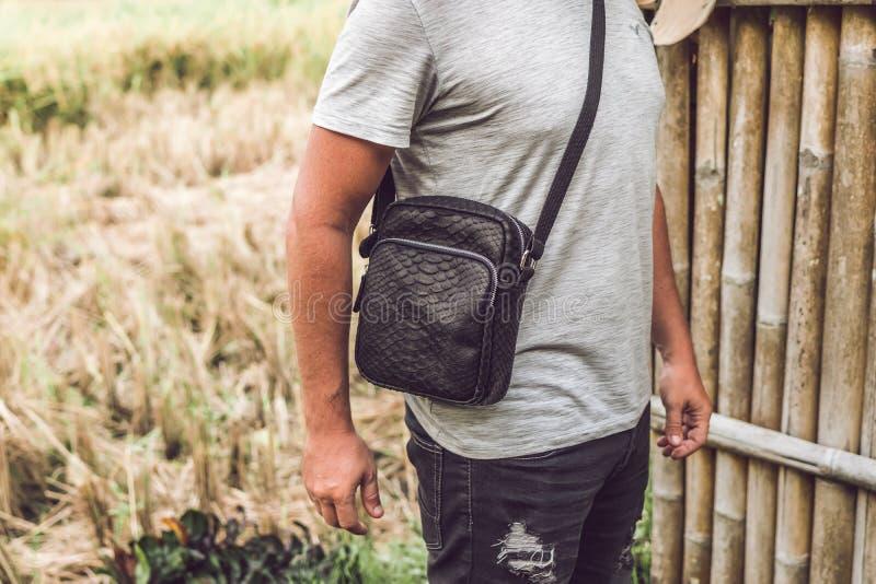 Mann mit Luxus-snakeskin Pythonlederhandtasche Bali-Inselhintergrund stockfotografie