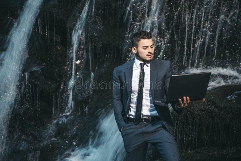 Mann mit Notizbuchstand nahe Wasserfall Moderne Technologie Erfolgreicher Geschäftsmann Fluss folgen Formaler Artgriff des Kerls stockfotografie