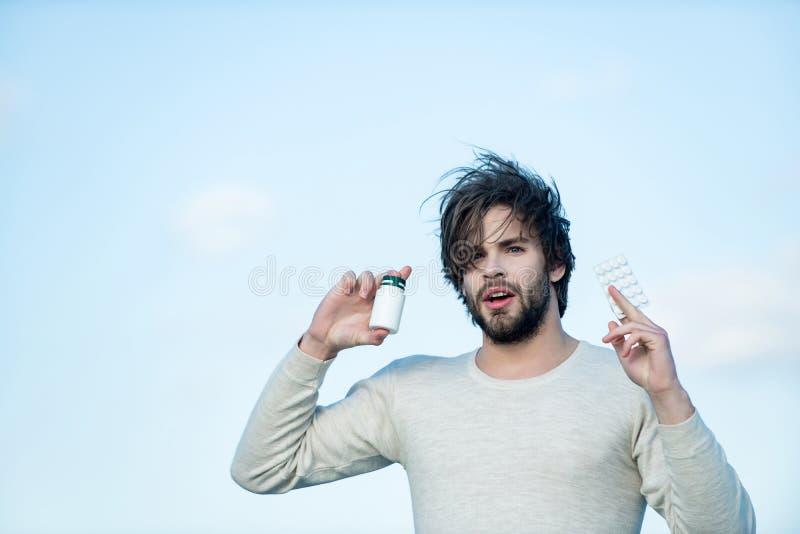 Mann mit Pillen im Glas und in der Blisterpackung stockbild