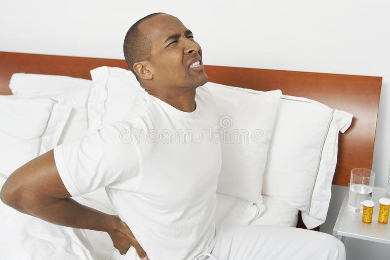 Mann mit Rückenschmerzen im Bett stockbilder