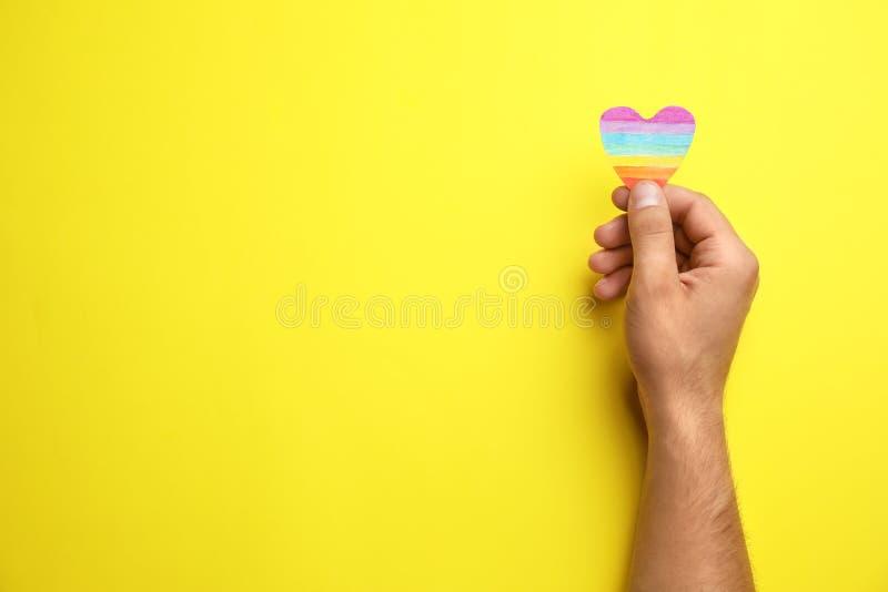 Mann mit Regenbogenherzen auf gelbem Hintergrund, Draufsicht Homosexuelles Symbol stockfotografie