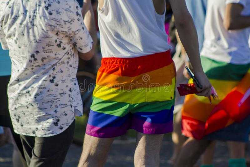 Mann mit Regenbogenkurzen hosen an einem homosexuellen Stolz LGBT lizenzfreie stockbilder