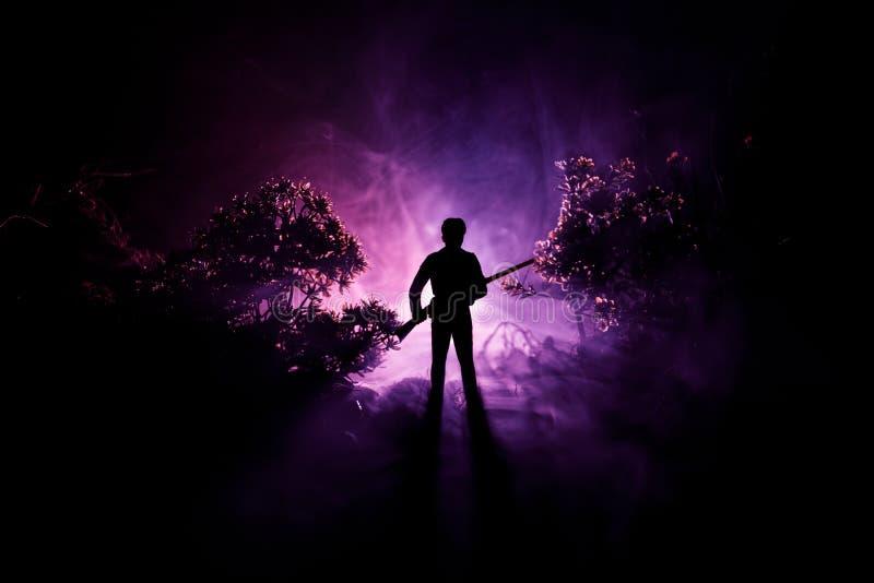 Mann mit Riffle am gespenstischen Wald nachts Merkwürdiges Schattenbild des Jägers in einem dunklen gespenstischen Wald nachts, m stockbilder