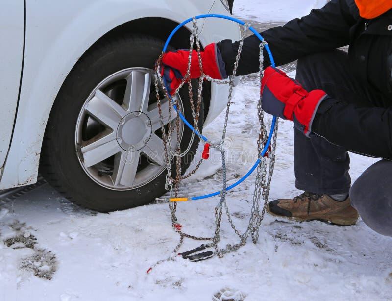 Mann mit roten Handschuhen installieren Schneeketten stockbild