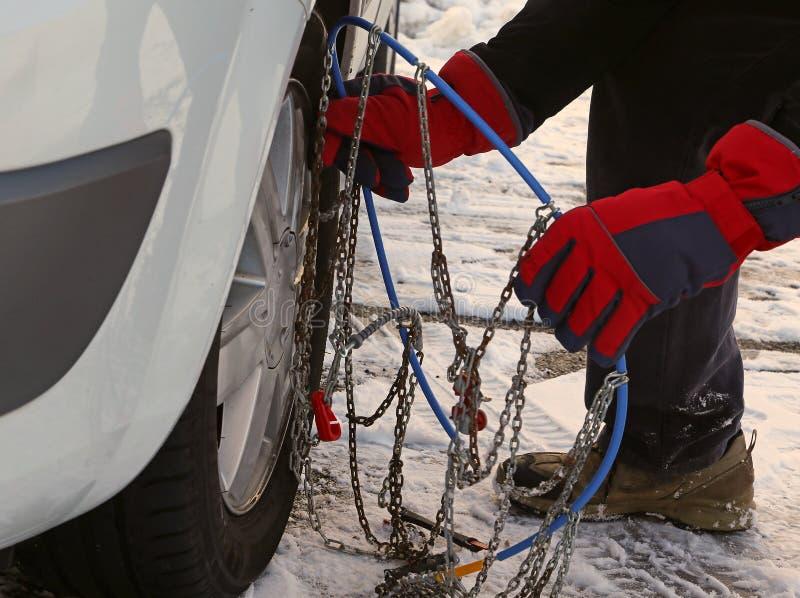 Mann mit roten Handschuhen installieren Schneeketten in den Autoreifen lizenzfreies stockfoto