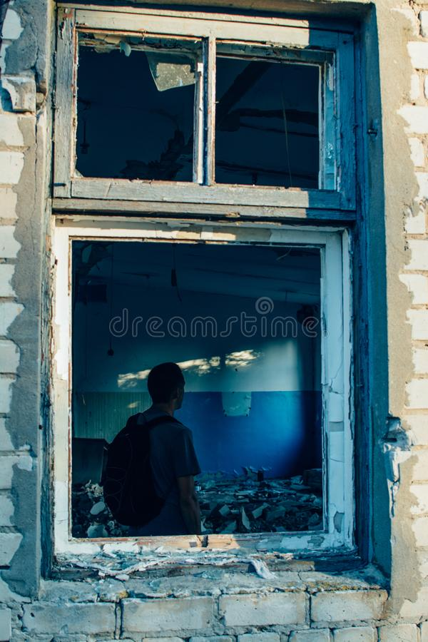 Mann mit Rucksack in ruiniertem zerstörtem Altbaufensterrahmen stockfotos