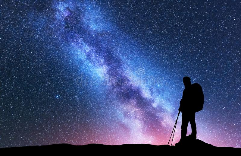 Mann mit Rucksack und Wanderstöcken gegen Milchstraße stockfotografie