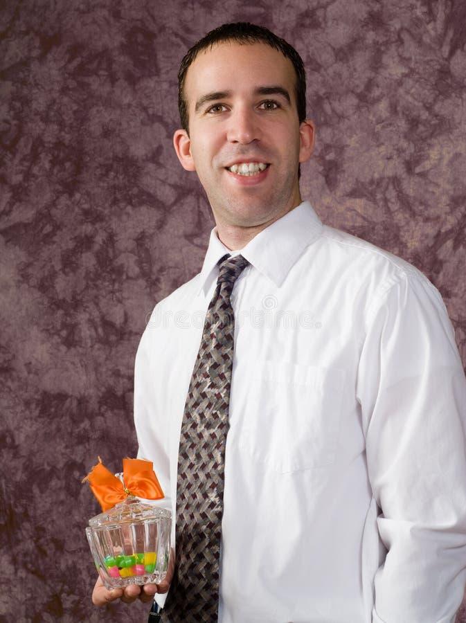 Mann mit Süßigkeitteller stockbild