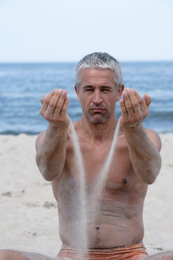 Mann mit Sand in den Händen lizenzfreie stockfotografie