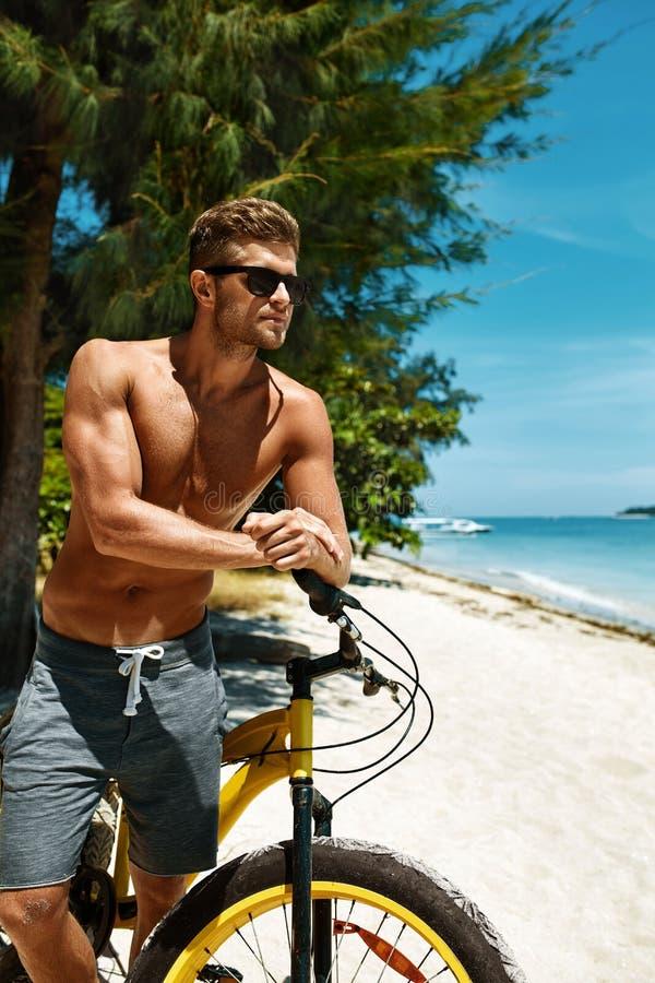 Mann mit Sand-Fahrrad auf Strand Sommer-Reise-Ferien genießend lizenzfreie stockfotografie