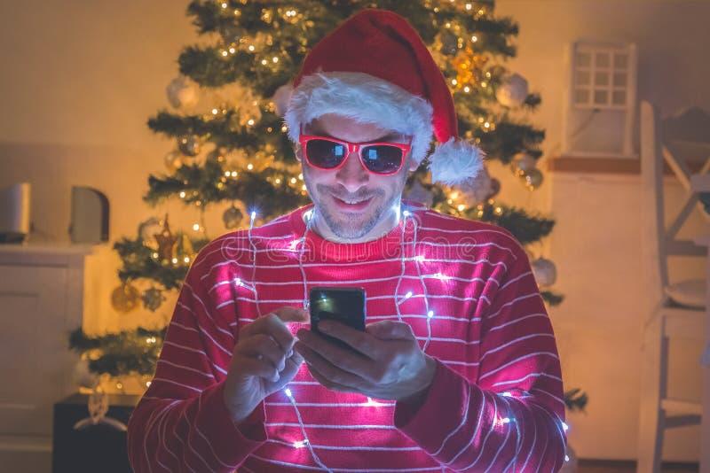 Mann mit Sankt-Hut- und -weihnachtslichtern unter Verwendung des Smartphone Weihnachtsbaum im Hintergrund stockfotos