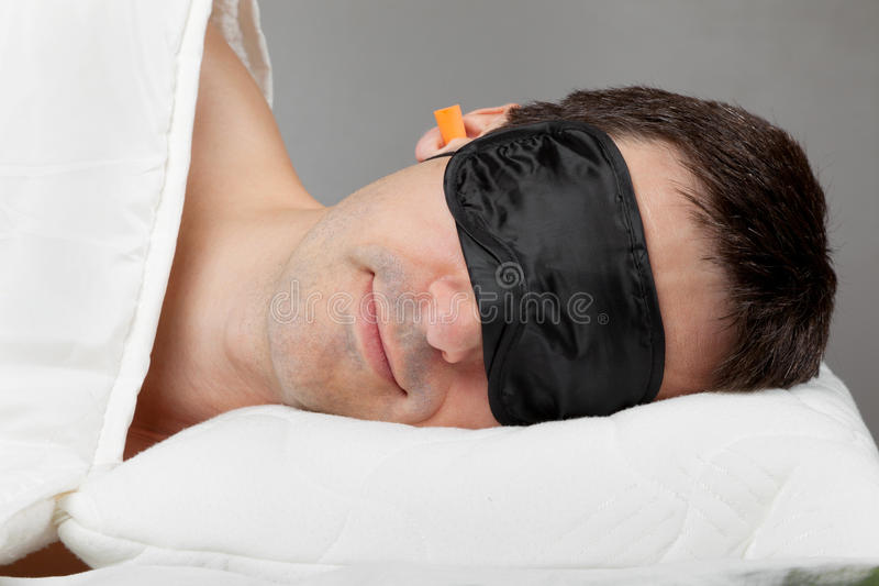Mann mit Schlafenschablone und Ohrenpfropfen im Bett stockfotografie