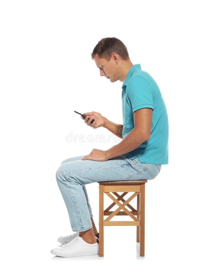 Mann mit schlechter Lage unter Verwendung des Smartphone beim Sitzen auf Schemel stockfotografie