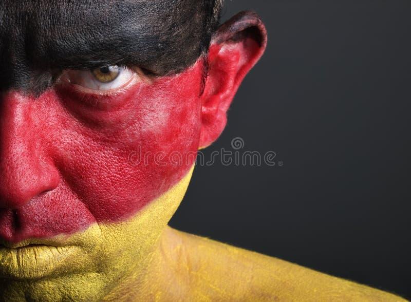 Mann mit seinem Gesicht gemalt mit der Markierungsfahne von Deutschland lizenzfreie stockfotografie