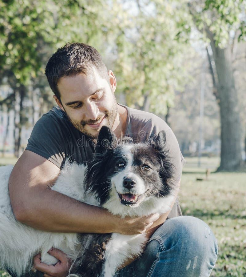 Mann mit seinem Hund, der im Park spielt lizenzfreies stockbild