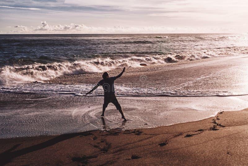Mann mit seinen Händen oben zur Sonnenuntergangzeit auf dem Strand lizenzfreie stockfotografie