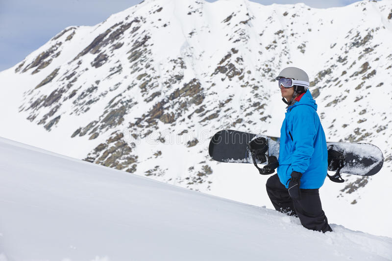 Mann mit Snowboard auf Ski Holiday In Mountains stockfoto