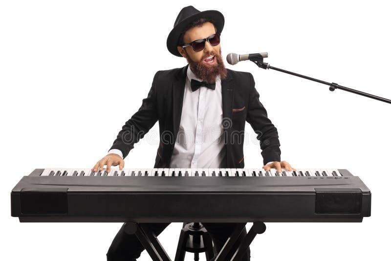 Mann mit Sonnenbrille und ein Bart, der ein Digitalpiano spielt und auf einem Mikrofon singt lizenzfreies stockfoto