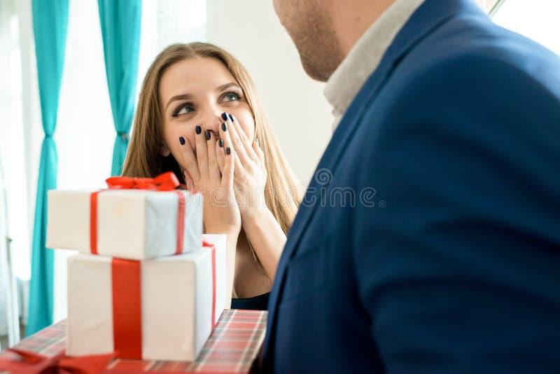 Mann mit Stapel Geschenken für Freundin stockbilder