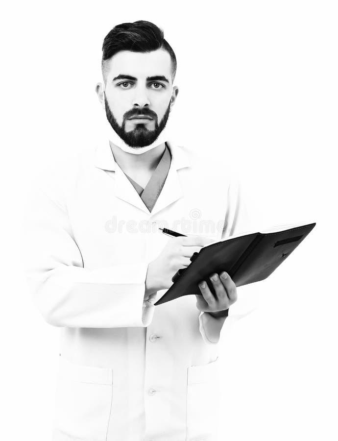 Mann mit starkem Gesicht im weißen Mantel und in der chirurgischen Maske stockbild