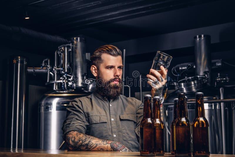Mann mit stilvollen Bart und dem Haar hält das halbe Liter Handwerksbier sitzend am Barzähler in der indie Brauerei stockfotos