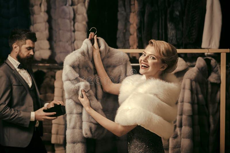Mann mit strengem Gesicht und Frau mit Mänteln im Pelzgeschäft stockbild