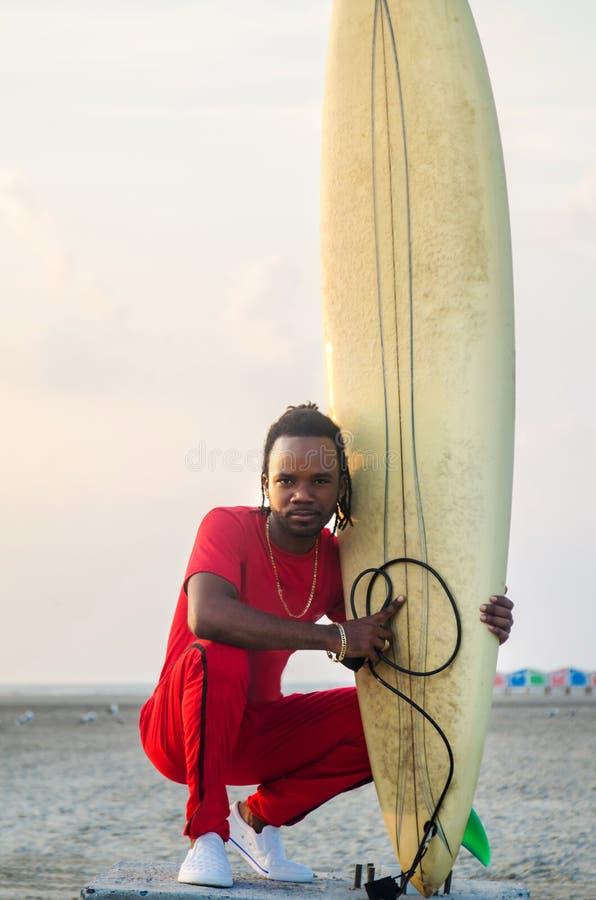 Mann mit Surfbrett auf dem Strand stockfotos
