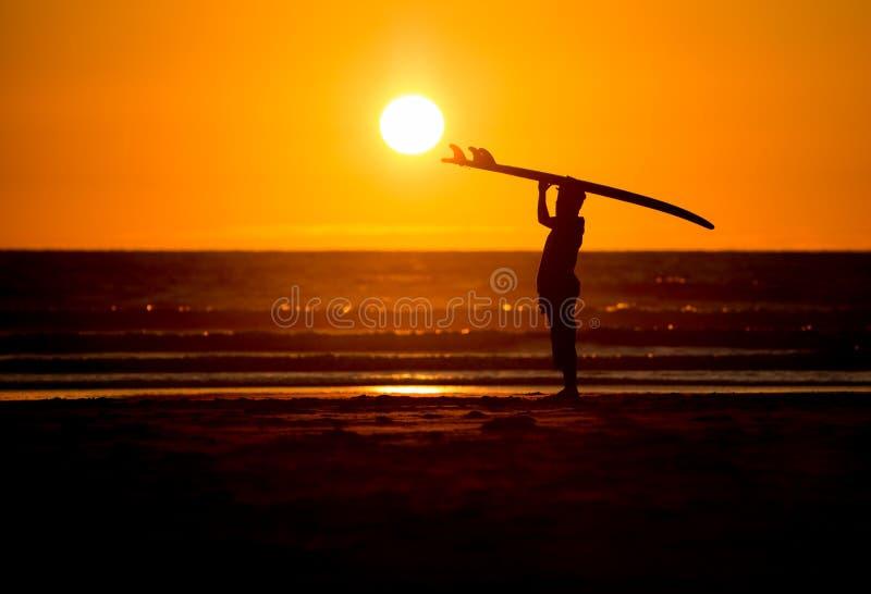Mann mit Surfbrett im Sonnenuntergang am Strand lizenzfreies stockbild