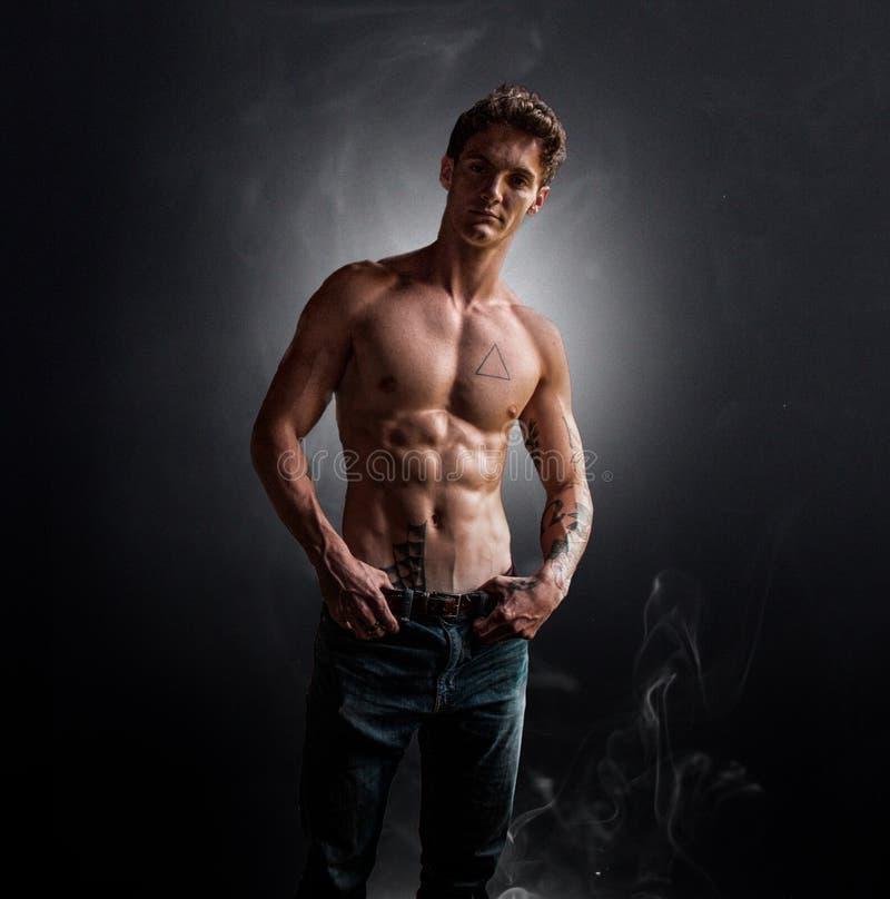 Mann mit Tätowierungen im Rauche lizenzfreie stockfotos