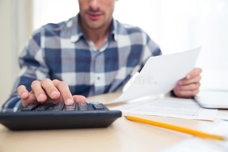 Mann mit Taschenrechner Rechnungen überprüfend lizenzfreie stockbilder