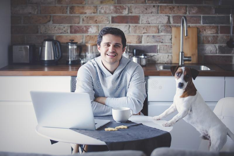 Mann mit Tasse Tee oder Kaffee und Laptop-Computer lizenzfreie stockfotografie