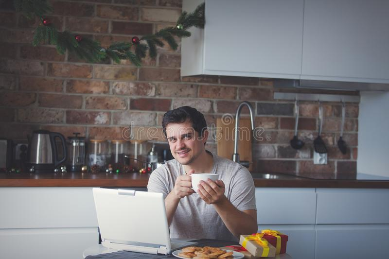 Mann mit Tasse Tee oder Kaffee und Laptop-Computer stockfoto